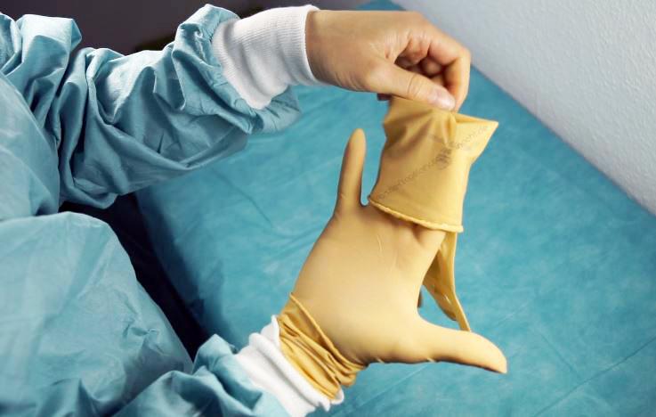 Vorsichtiges überziehen des zweiten sterilen Handschuhs.franzis-Blogstory.schreibnacht.de